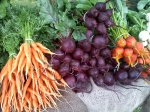 Fresh organic carrots and beets piled high.