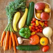 Organic Carrots, Cucumber, Garlic, Green Pepper, Summer Squash, Zucchini, Cherry Tomatoes, Heirloom Tomatoes, Walla Walla Onion, Potatoes on a burlap cloth.
