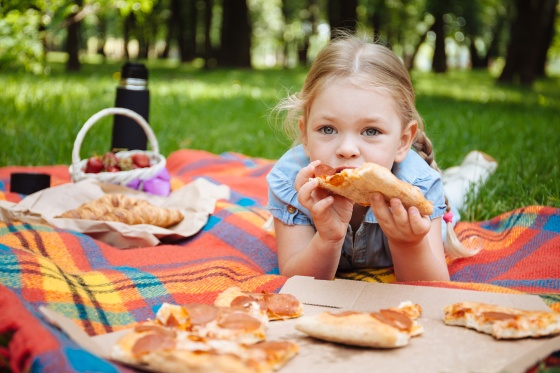 Little baby girl eating pizza and laughing outdoors on the background of green grass, summer picnic. Rest in the park.