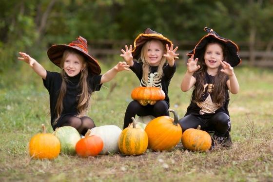 Group of happy kids in carnival costumes with Halloween pumpkin  at country farm on warm autumn day.